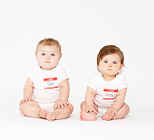 Two babies (6-9 months) sitting on white background