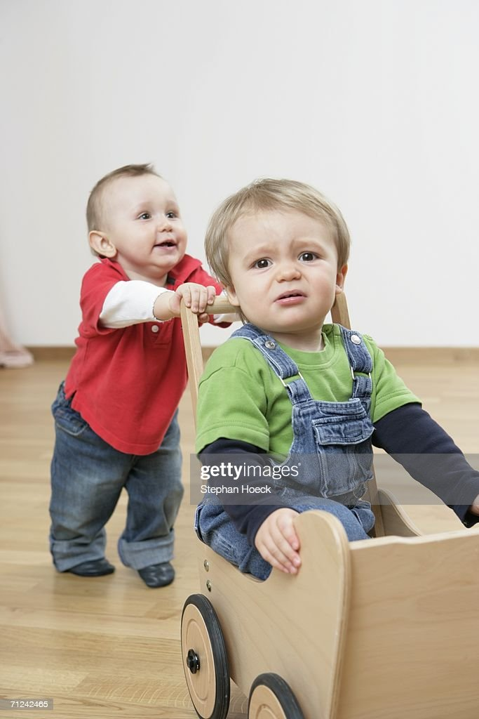 Two baby boys playing together : Stock Photo