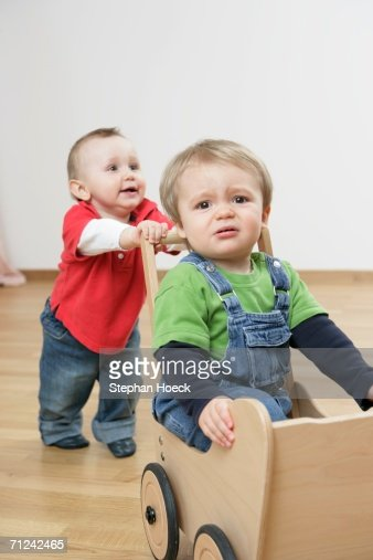 Two baby boys playing together : Bildbanksbilder