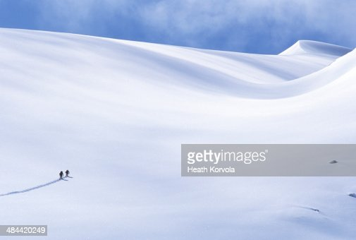 Two backcountry skiers make their way uphill.