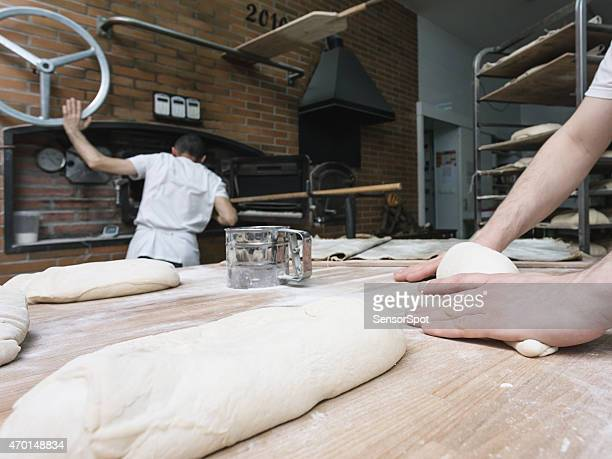 Two bakers kneading a bread dough and cooking bread