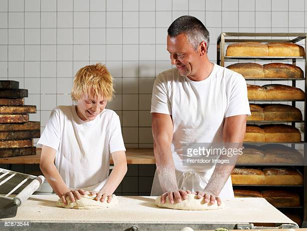 Two bakers kneading dough on floured surface