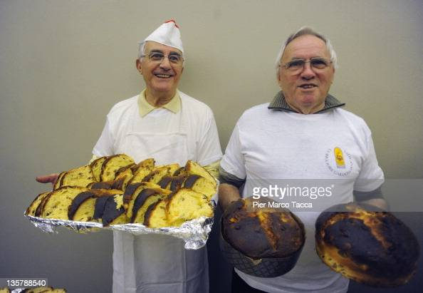 Two bakers show Panettone typical Italian Christmas cake during a Christmas party at Milan on December 14 2011 in Milan Italy