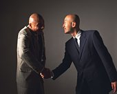 Two bald headed businessmen shaking hands, Side View