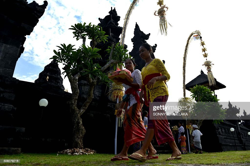 Two Balinese woman walk after they prayed at a temple to celebrate Galungan day in Jimbaran, on Indonesia's resort island of Bali on February 10, 2016. Galungan Day is a holiday celebrated by Balinese as a sign of victory of good against evil. AFP PHOTO/SONNY TUMBELAKA / AFP / SONNY TUMBELAKA