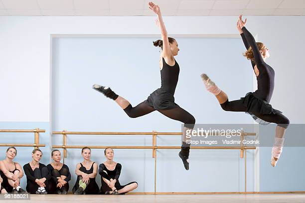 Two ballerinas leaping through the air as others look on