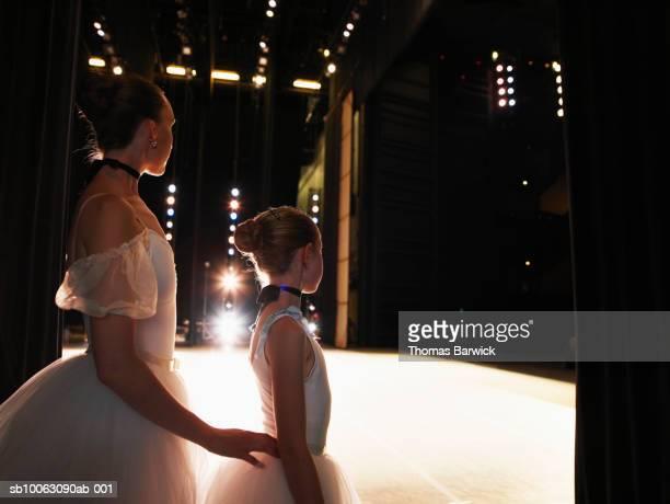 Two ballerinas standing in wings
