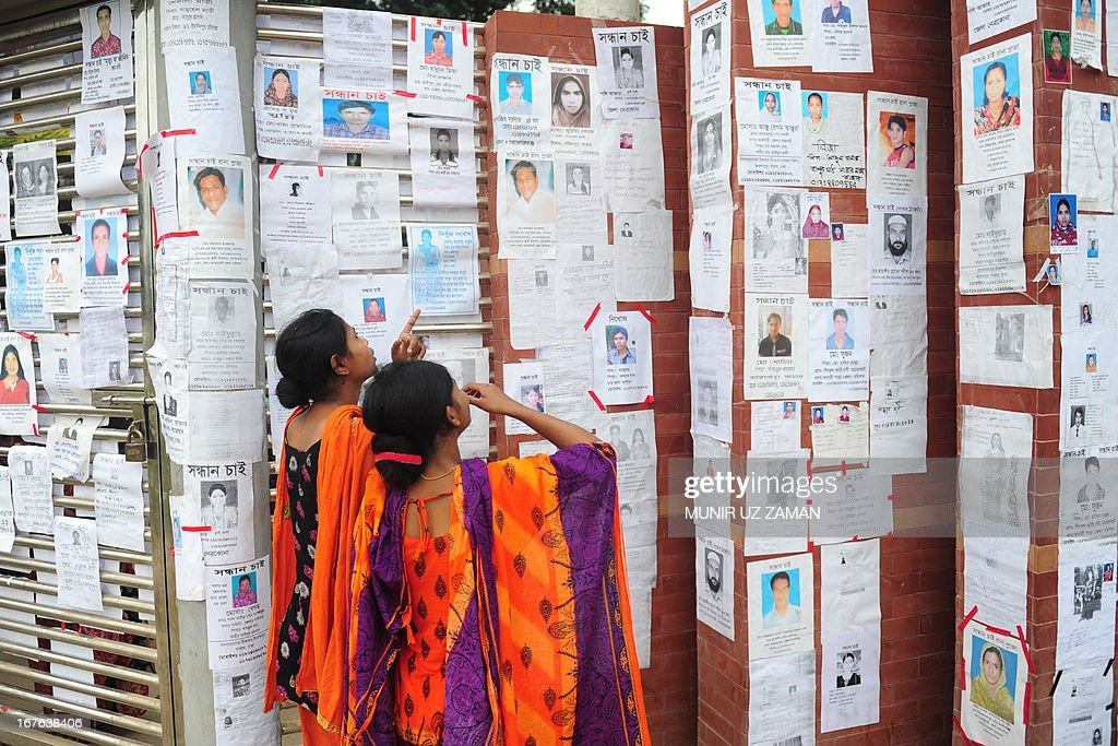 Two Bangladeshi women look at a board with notices posted of missing and dead workers three days after an eight-storey building collapsed in Savar, on the outskirts of Dhaka, on April 27, 2013. Police arrested two textile bosses over a Bangladeshi factory disaster as the death toll climbed to 332 and distraught relatives lashed out at rescuers trying to detect signs of life. AFP PHOTO/ Munir uz ZAMAN