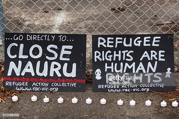 Two banners and candles at the gates of a refugee detention centre during a candlelight vigil as protestors stand in solidarity with refugees in...