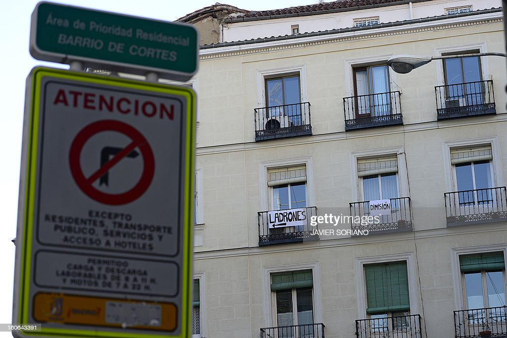 Two banners displayed on balconies read 'Thieves' (L) and 'Resignation' in front of the Spanish Congress in Madrid on February 4, 2013. Spain's ruling Popular Party said today it would take legal action against anyone who published or leaked information implicating its executives in a case of alleged corruption that has sparked calls for the prime minister to resign. AFP PHOTO/ JAVIER SORIANO