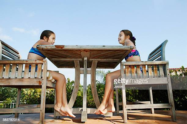 Two Barefooted Girls in Bikinis Sitting on Bench