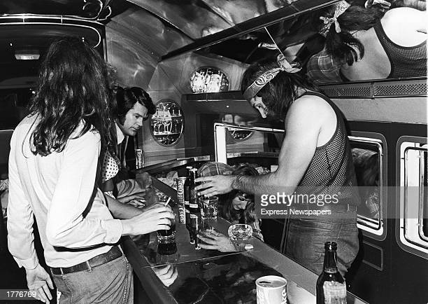 Two bartenders prepare drinks for guests at the bar aboard the British rock band Led Zeppelin's private jet July 30 1973