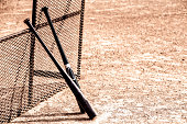 Two baseball bats leaning against a metal grated backstop on a shale covered baseball field