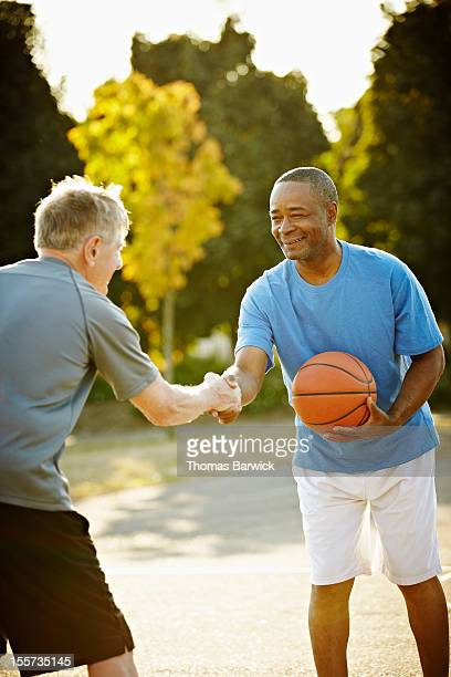 Two basketball players shaking hands smiling