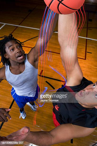 Two basketball players stretching to shoot ball, elevated view