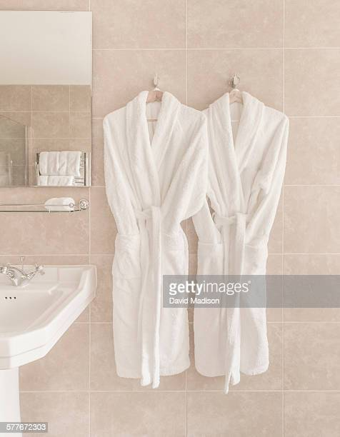 Two bathrobes hanging in bathroom