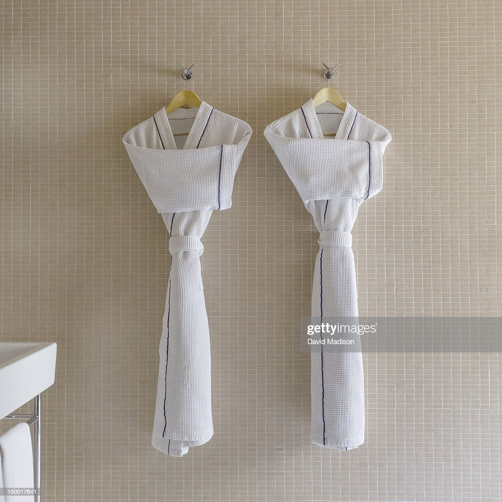 Two bathrobes hanging on hangers.