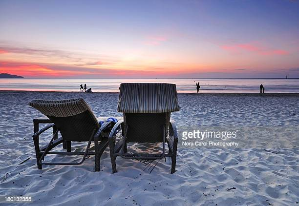 Two Beach Chair Facing the Sunset on a Sandy Beach