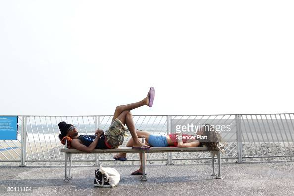 Two beach goers relax on a boardwalk bench in the late afternoon at Rockaway Beach on September 12 2013 in the Queens borough of New York City...