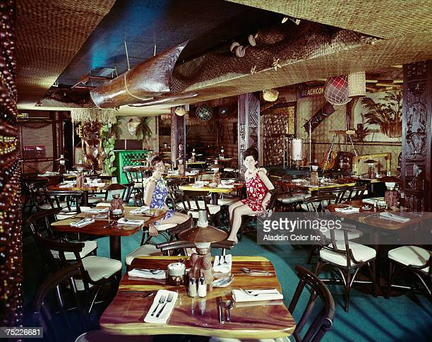 Two Beachcomber Hotel staff members both dressed in Hawaiianstyle flowerprint dresses sit in the hotel's Polynesian themed restaurant Harrisburg...