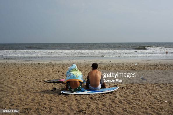 Two beachgoers relax in the late afternoon at Rockaway Beach on September 12 2013 in the Queens borough of New York City Despite the sustained damage...