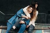 Two beautiful caucasian girls having fun laughing embracing.
