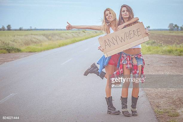 Two beautiful cheerful hipster friends hitchhiking by the road