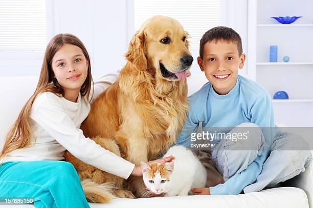 Two beautiful children enjoying with pets