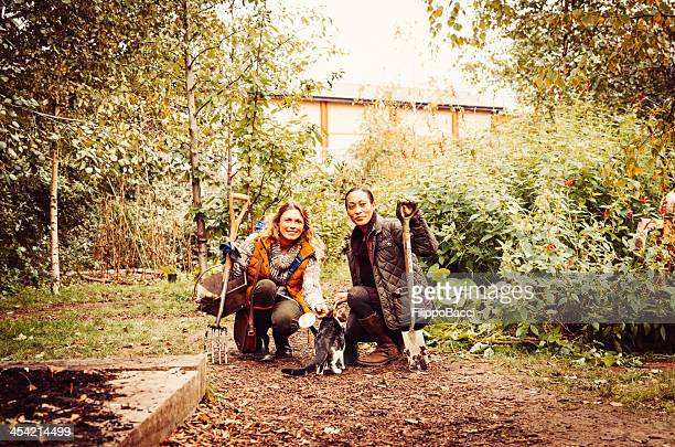 Two Beautiful Gardeners With A Cat In The Garden