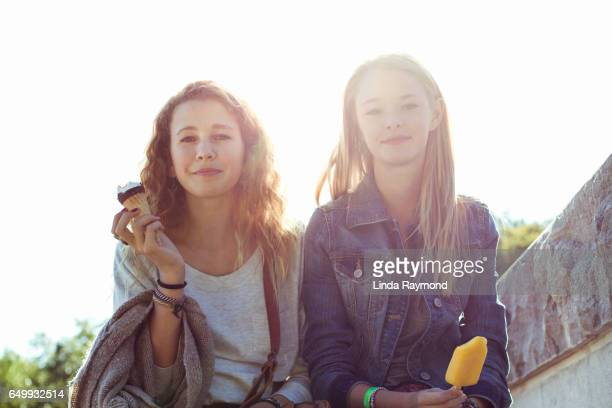 Two beautiful giril eating ice cream cone and popsicle in sunflare