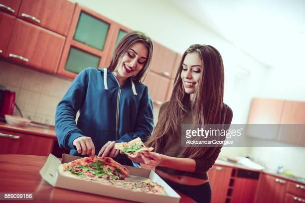 Två vackra flickor äta Pizza hemma för Lunch