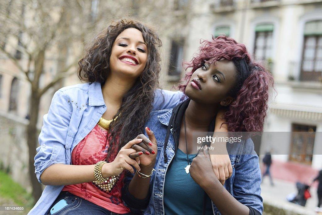 Dos hermosas chicas en urban backgrund, negro y se mezclan mujeres : Foto de stock