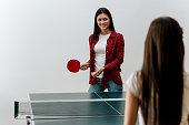 Two beautiful girls playing table tennis.
