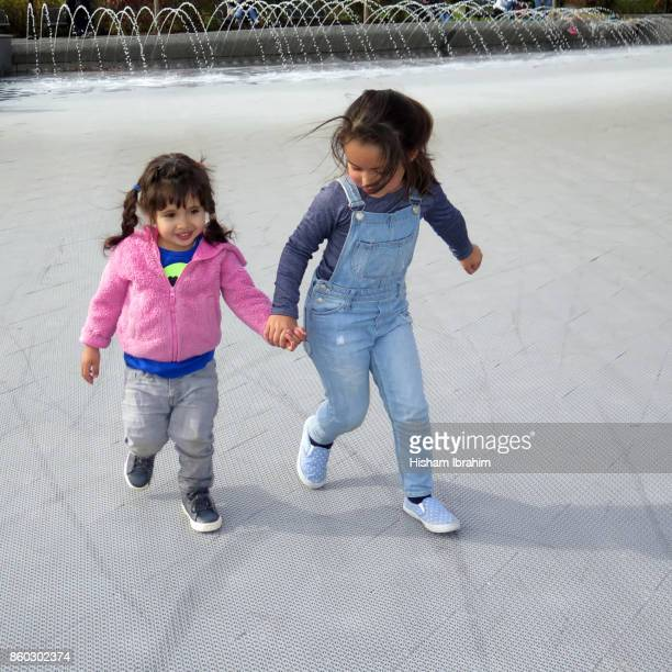 Two beautiful sisters 3 years and 5 years old holding hands and walking by a water fountain.