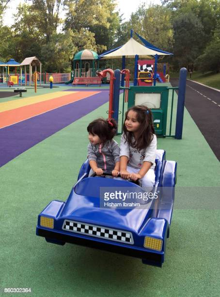 Two beautiful sisters 3 years and 5 years old riding a blue spring ride car in playground.