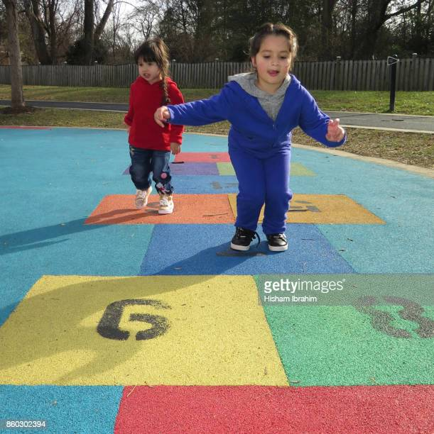 Two beautiful sisters 3 years and 5 years playing Hopscotch Game at playground.