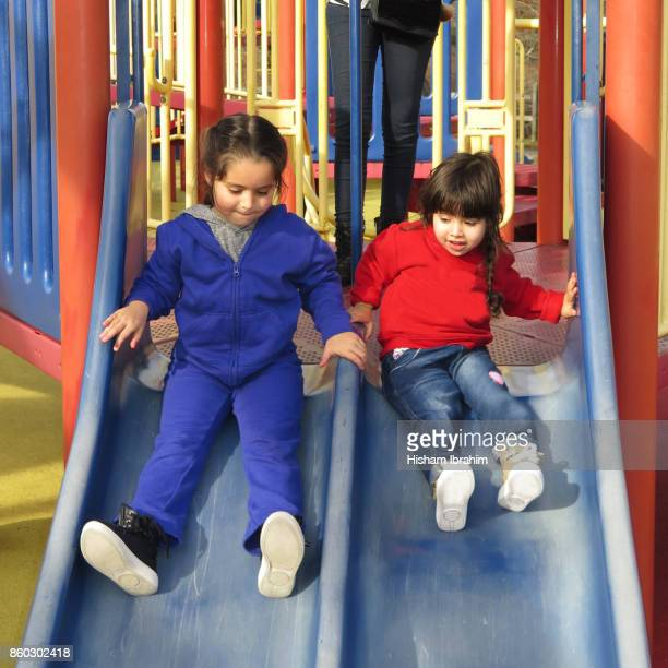 Two beautiful sisters 3 years and 5 years playing on slide at playground.