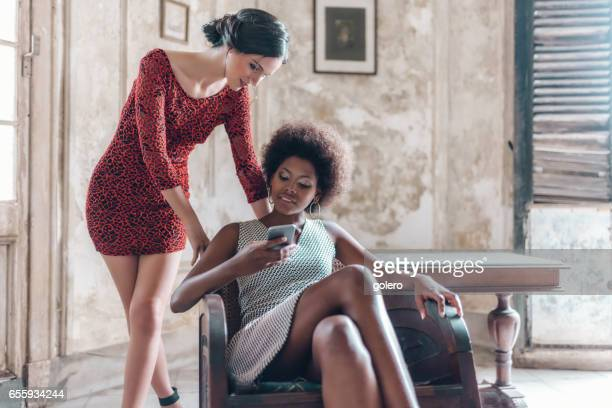 two beautiful stylish  young cuban woman looking at mobile indoors