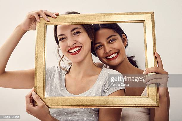 two beautiful woman holding golden frame