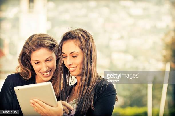 Duas belas mulheres olhando para tablet digital
