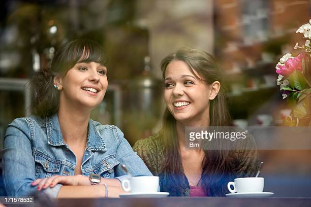 Two Beautiful Women Sitting in Cafe, Smiling, View Through Glass