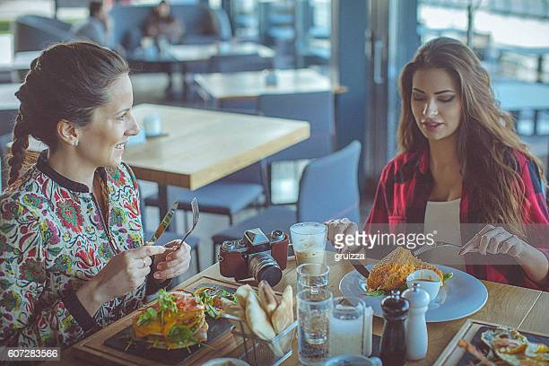 Two beautiful young women have breakfast at a fancy restaurant