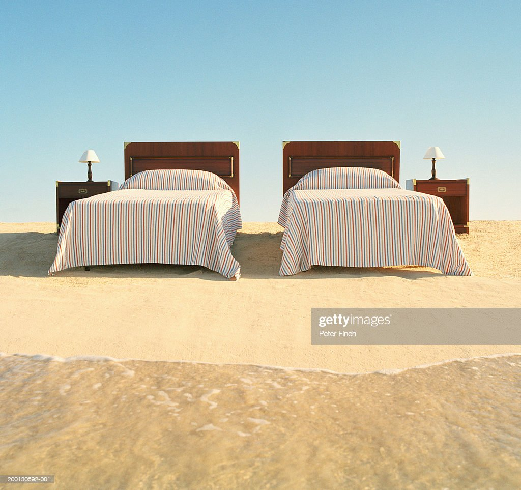 Two beds with bedside tables on beach by surf
