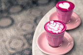 Two Beetroot latte are on standing in the pink cups and plates on white marble background. Trendy colorful red velvet drink with milk on the art floor