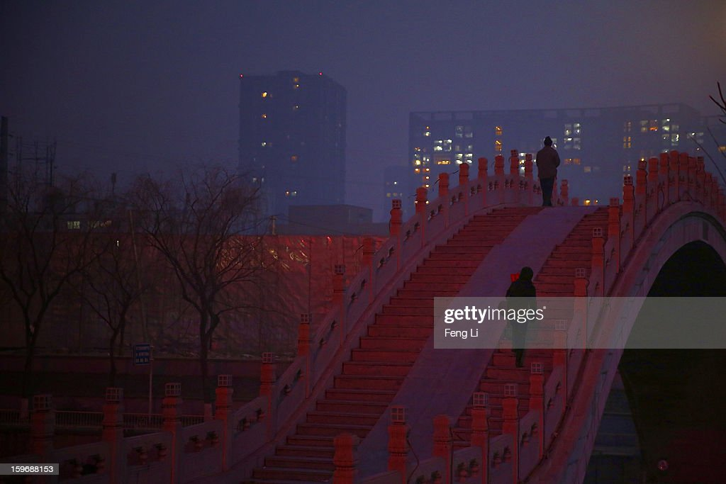 Two Beijing residents walk on a bridge during severe pollution on January 18, 2013 in Beijing, China.