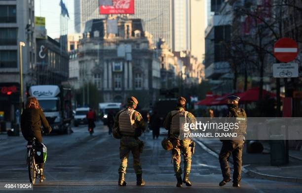 Two Belgian soldiers and a policeman patrol in Brussels on November 23 2015 as the Belgian capital remains on the highest possible alert level...