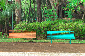 Two benches side by side on a square with trees and a beautiful green vegetation background. Orange and blue bench, very peaceful place to sit and relax with friends, choose one.