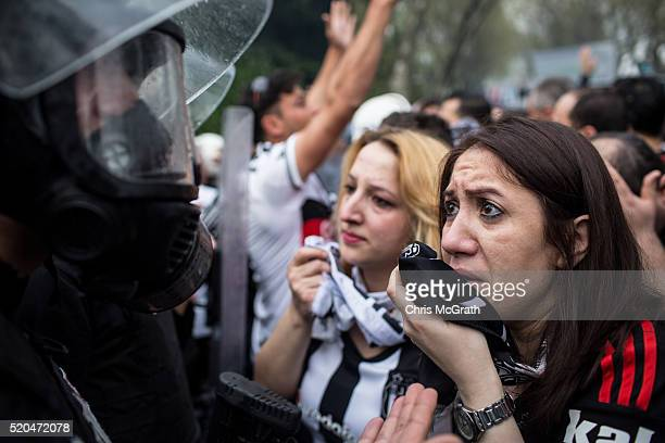 Two Besiktas fans cover their faces as they talk to police after tear gas was used to disperse fans trying to enter the stadium ahead of the opening...