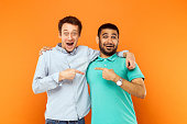 Two best friends hugging, pointing finger each other and looking at camera with shocked face. Studio shot on orange background