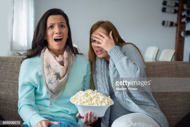 Two best friends sitting on sofa, eating popcorn, watching movie